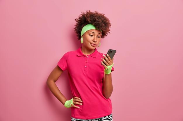 Mooie gekrulde haired jonge vrouw verzendt bericht op smartphone