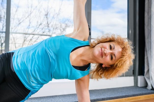 Mooie gekrulde middelbare leeftijd fit vrouw doet yoga fitness plank met brede handen, blij gezicht
