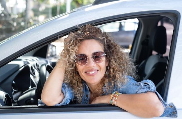 Mooie gekrulde vrouw in de auto leunend tegen het raam kijkend naar de camera glimlachend