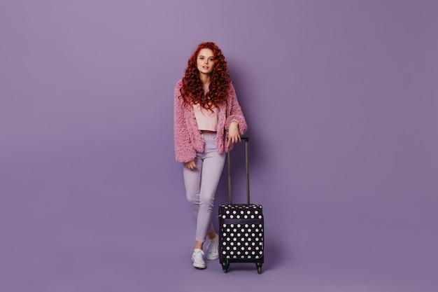 Mooie gekrulde vrouw in skinny jeans en roze jasje vormt met zwarte polka dot koffer.