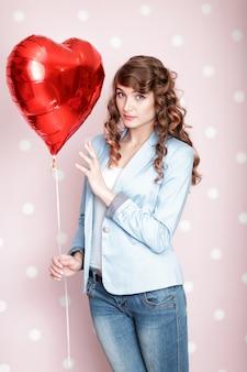 Mooie gekrulde vrouw met hartvormige luchtballonnen voor valentijnsdag