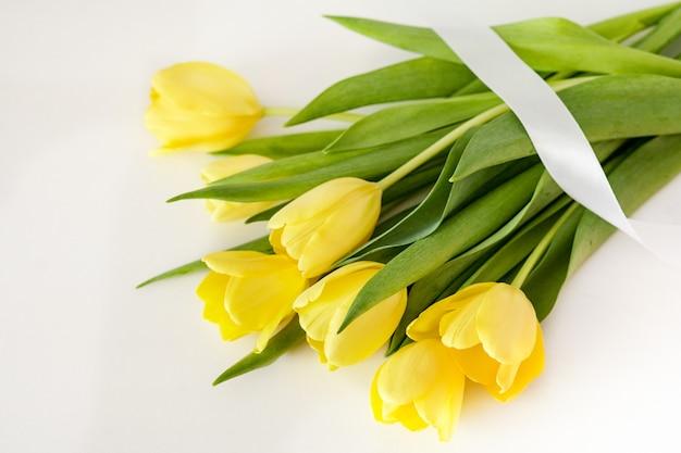 Mooie gele tulpen op een witte achtergrond. lentebloemen, bovenaanzicht. moeder en vrouwendag concept