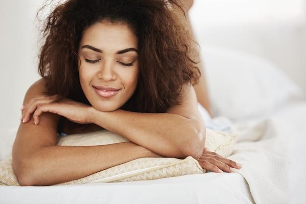 Mooie gelukkig afrikaanse vrouw met gesloten ogen glimlachen liggend op bed.