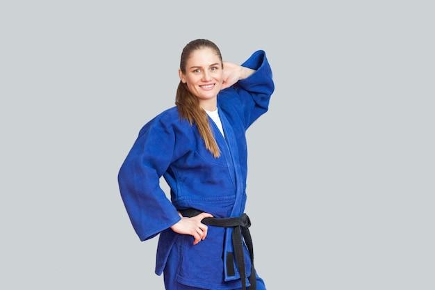 Mooie gelukkig atletische karate vrouw in blauwe kimono met zwarte gordel poseren en hand achter haar hoofd kijken camera. japans vechtsportenconcept. binnen, studio-opname, grijze achtergrond