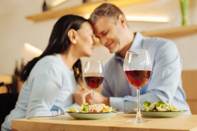 Mooie gelukkig gehandicapte vrouw en een aantrekkelijke glimlachende goedgebouwde man zitten in een café met gesloten ogen en hand in hand en aan het eten
