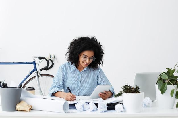 Mooie gelukkig gemengd ras vrouwelijke architect glimlachen, berekeningen opschrijven vanaf digitale tablet