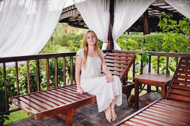 Mooie gelukkig jonge slanke langharige blonde meisje in tuinhuisje. houten installaties recreatie. vakantie. tuinhuis.
