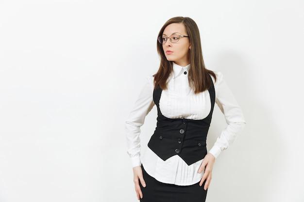 Mooie gelukkig kaukasische jonge lachende bruin-haar zakenvrouw in zwart pak, wit overhemd en bril op zoek opzij geïsoleerd op een witte achtergrond. manager of werknemer. kopieer ruimte voor advertentie.