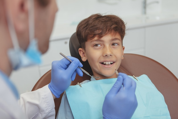 Mooie gelukkig kind lachend met gezonde tanden, krijgt zijn tandheelkundig onderzoek