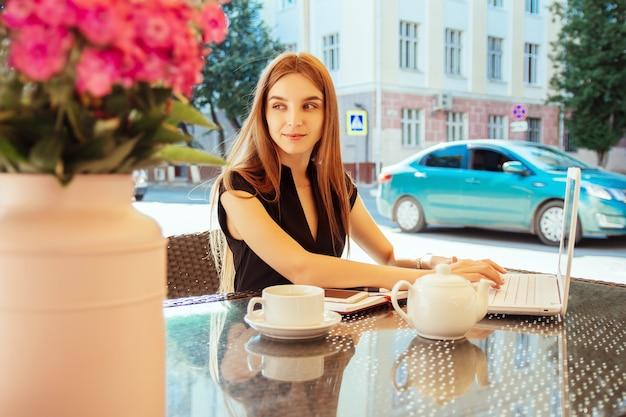 Mooie, gelukkig lachende jonge blanke vrouw die in een straatcafé aan een tafel zit en op een laptop werkt. het concept van werken op afstand, freelancen en online afstandsonderwijs.