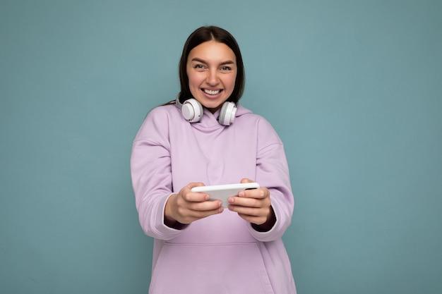 Mooie gelukkig lachende jonge brunette vrouw draagt paarse hoodie geïsoleerd op blauwe achtergrond