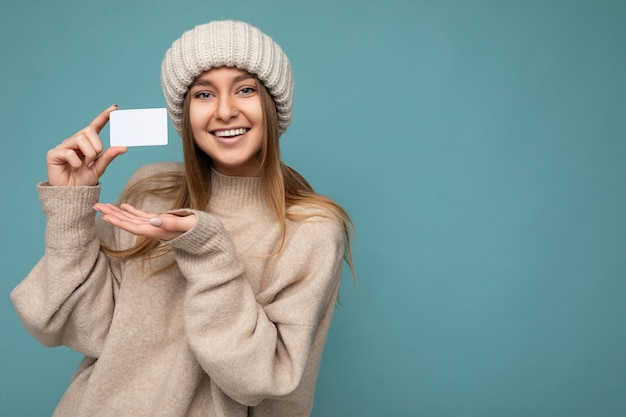 Mooie gelukkig lachende jonge donkere blonde vrouw dragen beige trui en gebreide beige hoed geïsoleerd over blauwe achtergrond houden en tonen creditcard camera kijken