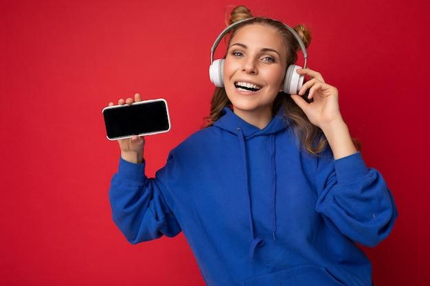Mooie gelukkig lachende jonge vrouw draagt stijlvolle casual outfit geïsoleerd op achtergrond muur