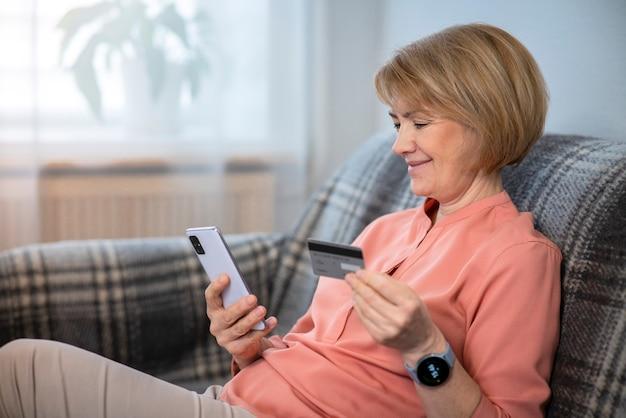 Mooie gelukkig positieve oudere senior vrouw thuis met mobiele telefoon, smartphone, kopen, gebruiken, creditcard in de hand houden voor internet winkelen, glimlachend. online betalingsconcept.