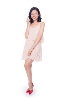 Mooie gelukkig schattige aziatische vrouw in casual roze jurk met rode lippen op witte achtergrond