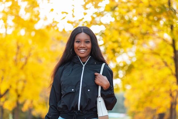 Mooie gelukkig zwarte lachende jonge vrouw in modieuze vrijetijdskleding met een jas, jeans en een handtas loopt in een herfstpark buiten. meisje op een achtergrond van felgeel gebladerte