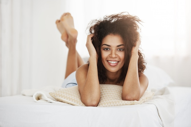 Mooie gelukkige afrikaanse vrouw die op bed ligt dat thuis glimlacht.