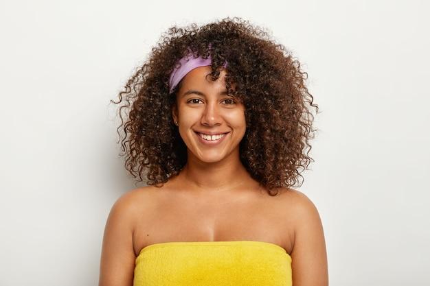 Mooie gelukkige afro-vrouw staat gewikkeld in een gele handdoek, voorbereid op sauna, heeft borstelig, knapperig haar, draagt een hoofdband, voelt zich tevreden om er altijd jong uit te zien. vrouwelijkheid, etniciteit en welzijnsconcept
