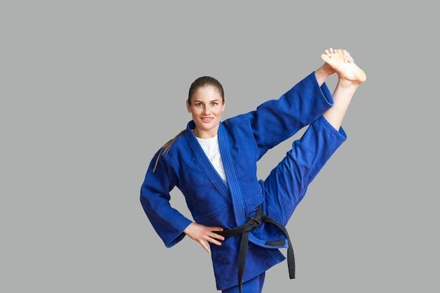 Mooie gelukkige atletische karatevrouw in blauwe kimono met zwarte riem die verticaal bindgaren maakt en camera met brede glimlach bekijkt. japans vechtsportenconcept. binnen, studio-opname, grijze achtergrond