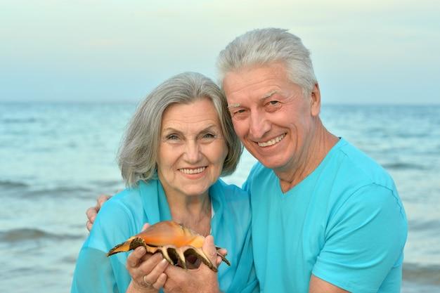 Mooie gelukkige bejaarde echtpaar rust in tropisch resort met shell