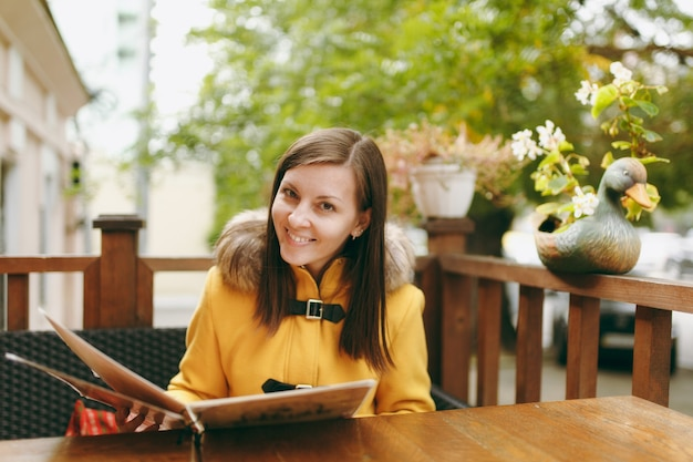 Mooie gelukkige blanke jonge lachende bruinharige vrouw in gele jas lezen, bestellen van menu in openluchtrestaurant of café in de buurt van de weg en beslissen wat te eten tijdens het diner in het herfstseizoen.
