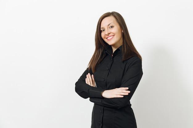 Mooie gelukkige blanke jonge lachende bruinharige zakenvrouw in zwart klassiek shirt en rok hand in hand gekruist geïsoleerd op een witte muur