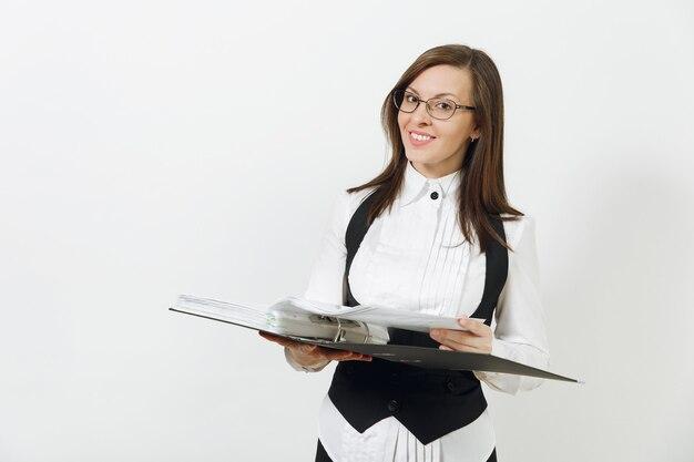 Mooie gelukkige blanke jonge lachende bruinharige zakenvrouw in zwart pak, wit overhemd en bril met map met werkdocumenten geïsoleerd op een witte muur