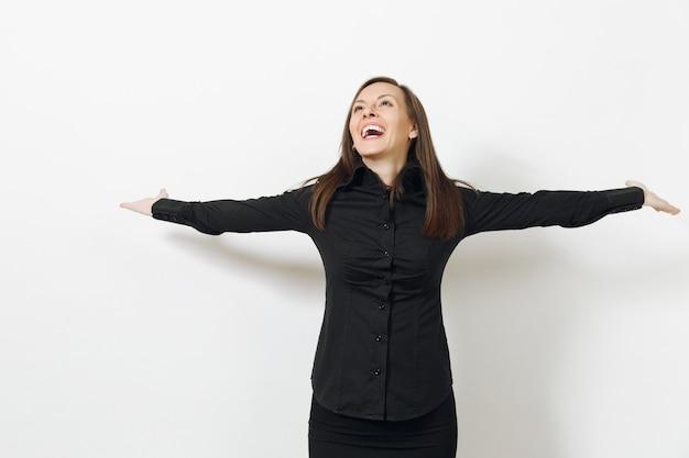 Mooie, gelukkige blanke jonge lachende zakenvrouw met bruin haar in een zwart klassiek shirt en rok die handen uitspreiden die op een witte muur zijn geïsoleerd