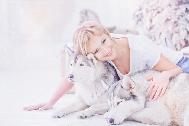 Mooie gelukkige blonde vrouw zittend op de vloer en knuffelen twee husky honden in de buurt van de kerstboom. gelukkig kersttijdconcept.