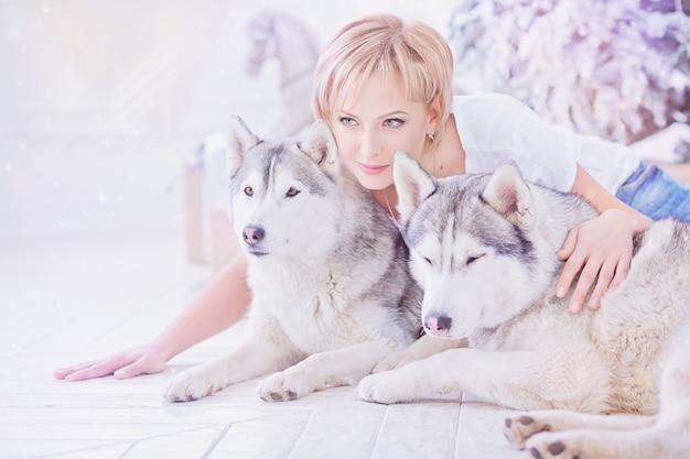 Mooie gelukkige blonde vrouw zittend op de vloer en knuffelen twee husky honden in de buurt van de kerstboom. gelukkig wintervakantieconcept.