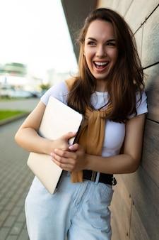 Mooie gelukkige donkerbruine jonge vrouw die aan kant in de straat met laptop computer in handen kijkt