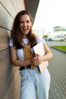 Mooie gelukkige donkerbruine jonge vrouw die aan kant in de straat met laptop computer in handen met wit t-shirt en spijkerbroek kijkt.