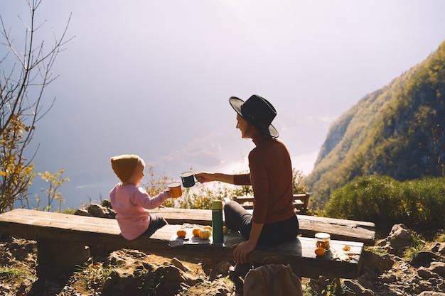 Mooie gelukkige familie buitenshuis moeder en dochter op een picknick in de bergen