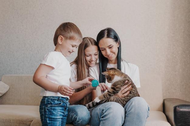 Mooie gelukkige familie moeder en twee kinderen spelen met een kat, zittend op de bank.