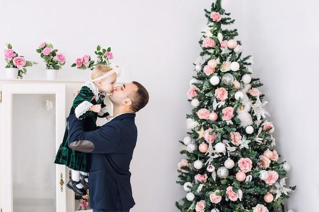 Mooie gelukkige familie vader en dochtertje samen thuis op vakantie bij de kerstboom