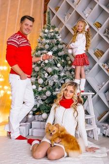 Mooie gelukkige familiemoeder, vader en dochter en kleine hond om kerstmis te vieren