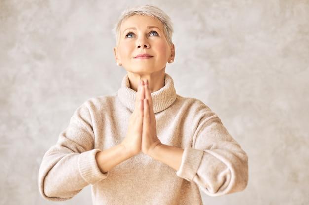 Mooie gelukkige gepensioneerde vrouw, gekleed in gezellige trui en kort kapsel bidden