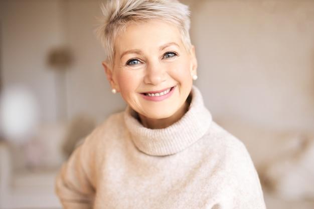 Mooie gelukkige gepensioneerde vrouw, gekleed in gezellige trui en kort kapsel