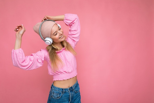 Mooie gelukkige glimlachende jonge blonde vrouw die roze geïsoleerde blouse en roze hoed draagt