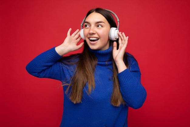 Mooie gelukkige glimlachende jonge donkerbruine vrouw die blauwe sweater draagt die over rode achtergrond wordt geïsoleerd