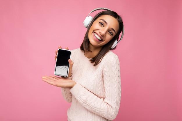 Mooie gelukkige glimlachende jonge vrouw die modieuze vrijetijdskleding draagt die op achtergrondmuur wordt geïsoleerd