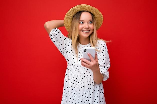Mooie gelukkige glimlachende jonge vrouw die vrijetijdskleding draagt die zich geïsoleerd over achtergrond bevindt die op internet surft via telefoon die aan de kant kijkt.