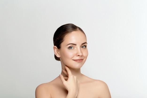 Mooie gelukkige glimlachende jonge vrouw met verse natuurlijke gezichtsmake-up op schoonheidsgezicht.