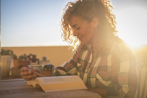 Mooie, gelukkige glimlachende ontspannende blanke krullende blonde vrouw die een boek leest terwijl ze de zonlichtzonsondergang op het terras buiten thuis leest