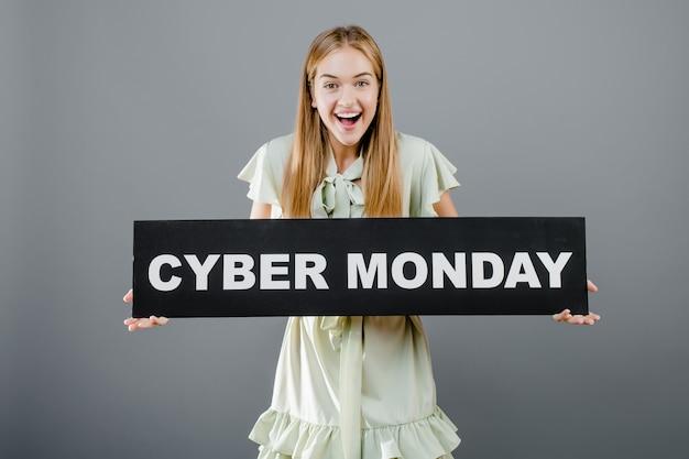 Mooie gelukkige glimlachende vrouw met geïsoleerd cybermaandagteken