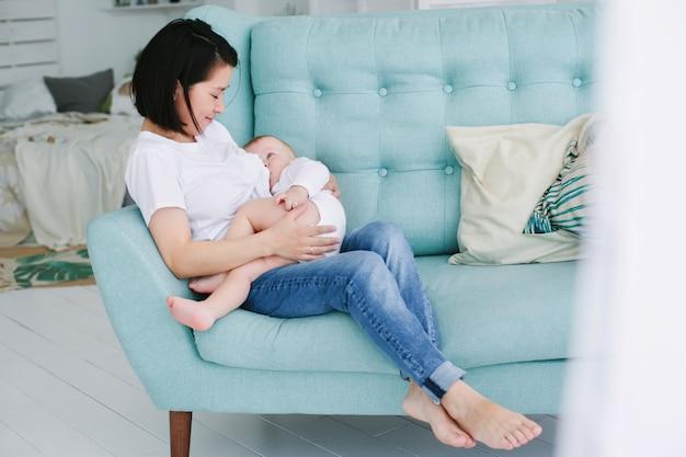 Mooie gelukkige jonge aziatische moeder die haar babydochter in slaapkamer knuffelt