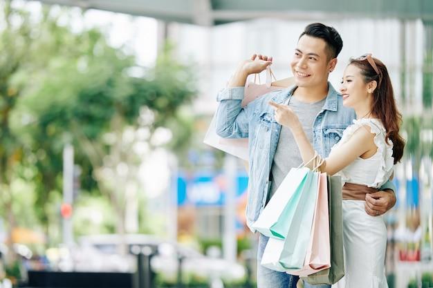 Mooie gelukkige jonge aziatische paar staande in de straat met boodschappentassen en wegkijken