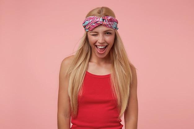 Mooie gelukkige jonge blonde vrouw poseren, glimlachen en knipogen, gekleurde hoofdband en rood shirt dragen
