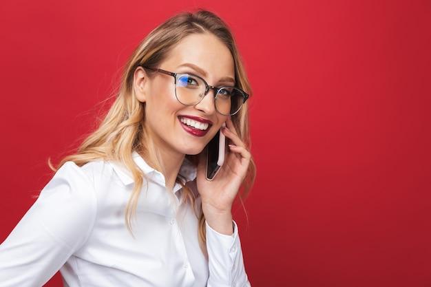 Mooie gelukkige jonge blonde vrouw stond geïsoleerd op rode achtergrond, met mobiele telefoon