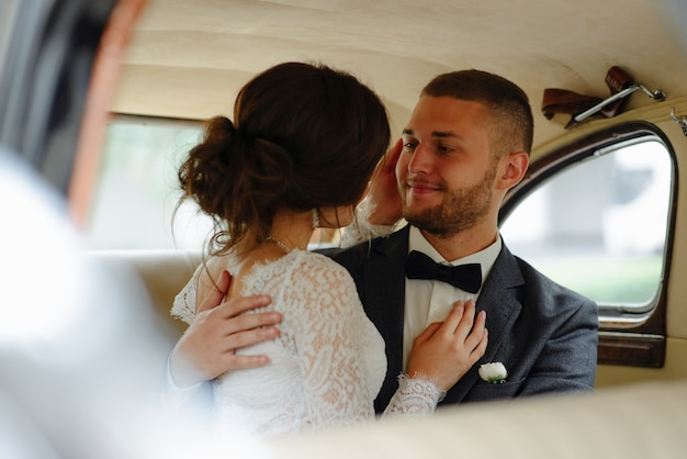 Mooie gelukkige jonge bruid en bruidegom die van retro auto kijken